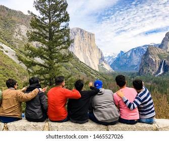 YOSEMITE NATIONAL PARK, CA - MARCH 31, 2018: Group of friends pointing at beautiful landscape Yosemite valley. Taken at Yosemite valley in Yosemite National Park, California, USA