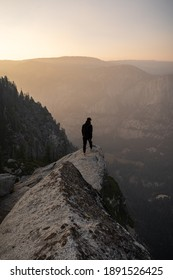 Yosemite National Park, CA USA - May 10 2020: A person standing on a cliff to look at the spectacular view of the Yosemite Valley.