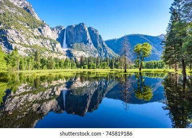 Yosemite National Park - Reflection in Merced River of Yosemite waterfalls and beautiful mountain landscape, hiking in the beautiful nature of California, USA