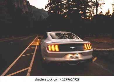 Yosemite National Park, USA. September 10, 2018.  Beautiful white Ford Mustang  GT parked in the heart of the Yosemite National park with amazing half dome cliffs around it.