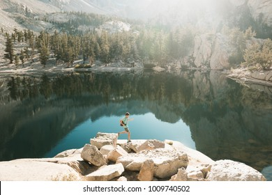 Yosemite NP, USA: Young sporty man runs and jumps on the rocks next to the mirror lake in high Sierra