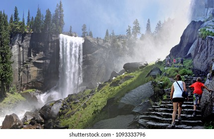 Yosemite, USA - July 26, 2011: two girls climbing stairs towards Vernal falls creating the mist to which the trail has been named: the mist trail. In the background more people are climbing higher up.