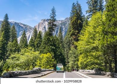 Yosemite village, California / USA - June 16 2017: tourist van on the tourist road in the Yosemite National Park, California, USA. Panorama of the Yosemite valley and Yosemite Falls in summer