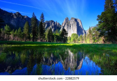 Yosemite's Cathedral Rocks and a blue sky, reflected in standing water.