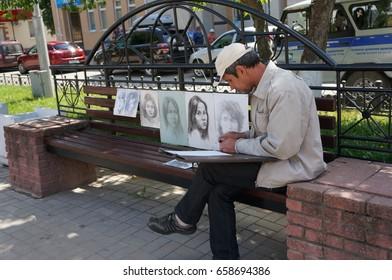YOSHKAR-OLA, RUSSIA, JUNE 12, 2017: Holiday Russia Day - An elderly artist paints portraits on the boulevard