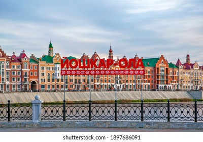 """YOSHKAR-OLA, RUSSIA - OCTOBER 27, 2020: Photo of An art object with an inscription in large letters """"Yoshkar-Ola"""" against the backdrop of the picturesque Bruges embankment, at sunset."""