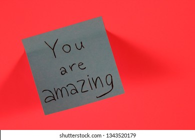You are amazing. Blue sticky note with inspirational quote on neon pink background. Handwritten positive reminder/advice. Concept for confidence, courage and motivation. Sign of moral support.