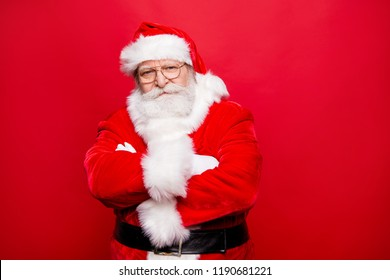 You behaved well in this year? Serious stylish Saint Nicholas in glass spectacles folded cross hands over chests look at camera with calm confident concentrated face isolated on shine red background