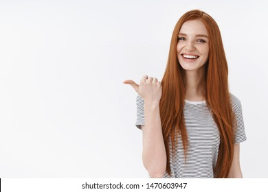 You better see it. Charming lively happy smiling redhead girl blue eyes pointing thumb left giving direction showing cool place hang out asking out friend drink coffee order take-away laughing