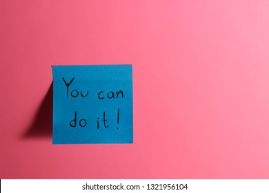 You can do it. Blue sticky note with inspirational quote on neon pink background. Handwritten positive reminder/advice. Concept for confidence, courage and motivation. Sign of moral support.