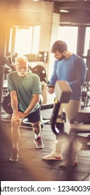 You can do it. Personal trainer giving support senior man at gym.