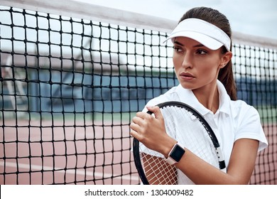 You can do it! Portrait of young beautiful woman with a racket on a court, looking away.