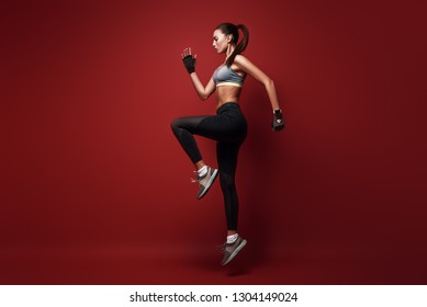 You can do it! Sportswoman jumping over red background, isolated