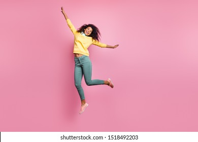 You can even fly up to the stars when enjoying favorite song! Full length photo of excited cheerful delightful crazy hipster jumping up stretching arms wear yellow sweatshirt pants isolated background