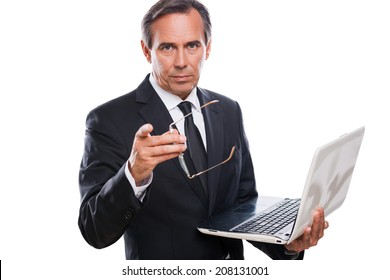 You can trust me! Confident mature man in formalwear holding laptop and pointing you while standing isolated on white background