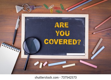Are You Covered. On a wooden table chalk board