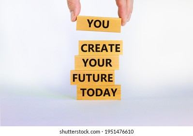 You create your future today symbol. Concept words 'You create your future today' on wooden blocks on a beautiful white background. Businessman hand. Business, motivational and create future concept.
