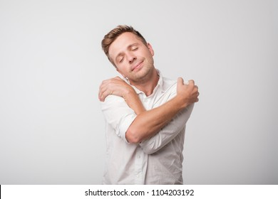 You do not need girlfriend if you can hug yourself. Concept of selfish feeling. Funny caucasian guy in white shirt cuddling himself and smiling from pleasure, closing eyes