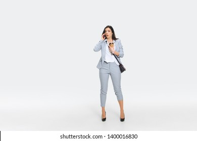 You are fired from yesterday. Young woman in gray suit is getting shocking news from boss or colleagues. Looking numbed while dropping coffee. Concept of office worker's troubles, business, stress.