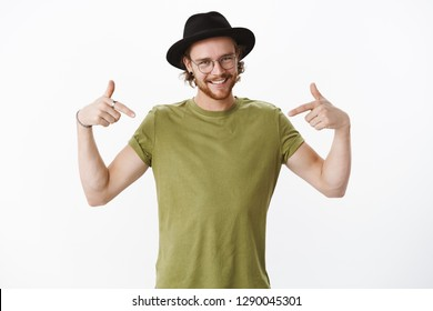 You found right guy, pick me. Confident, self-assured and charismatic male bearded actor in glasses and hat promoting himself as wanting role smiling broadly and pointing at body over gray wall