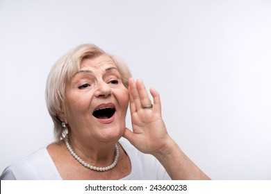 Are you getting the message. Closeup portrait of elderly woman putting her hand to mouth directing to copy space while standing against white background