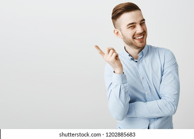 You got me. Happy charming male entrepreneur in formal blue shirt raising index finger and shaking forefinger at camera joyfully laughing and smiling at camera being pleased with good joke