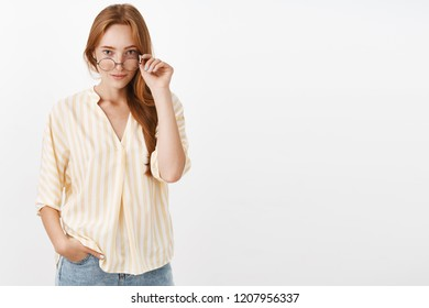You got my attention. Intrigued smart and creative female blogger with ginger hair and freckles taking off glasses and looking under rim with curious expression smirking hearing interesting news