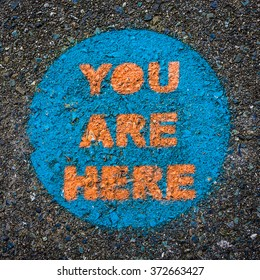 You Are Here. Funny circular public park sign painted on pavement pinpoints your location.