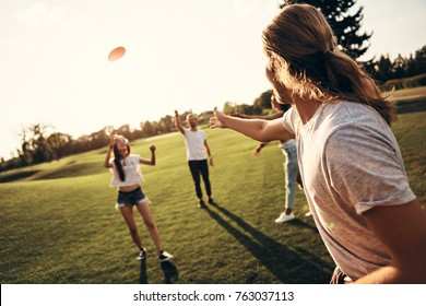 You just have to catch! Group of young people in casual wear playing while spending carefree time outdoors