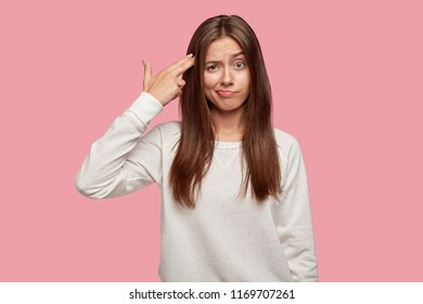 You are killing me! Exhausted student makes suicide gesture, shoots in temple, commits suicide, wears casual outfit, stands against pink background. Female feels bored, looks displeased at camera