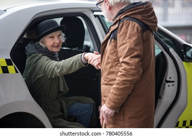 You are so kind. Old man is helping elegant senior woman to get out of taxi. She is looking at him gratefully. Focus on female