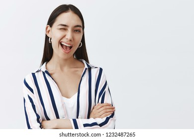 If you know what I mean. Confident and flirty cute woman in striped blouse, winking joyfully at camera, smiling broadly and holding hands crossed on chest in self-assured pose, hinting at something