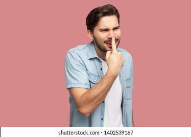 You are liar. Portrait of angry handsome bearded young man in blue casual style shirt standing, touching his nose and showing lie gesture. indoor studio shot, isolated on pink background.