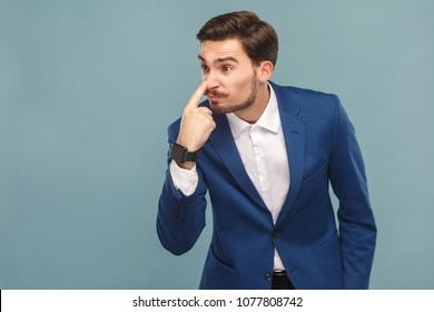 You lie! Anger businessman pointing finger at nose. Business people concept, richly and success. Indoor, studio shot on light blue background