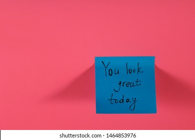 You look great today. Blue sticky note with inspirational quote on neon pink background. Handwritten positive reminder/advice. Concept for confidence, courage and motivation. Sign of moral support.