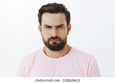 You look suspicious. Portrait of intense serious-looking handsome man with beard, frowning and squinting, showing disbelief or doubt, being unsure if person telling truth, blaming or judging with gaze