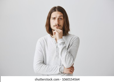 You made me interested and curious, tell details. Portrait of handsome young male with beard and long hair holding hand on chin and lifting eyebrow intrigued, standing over gray background