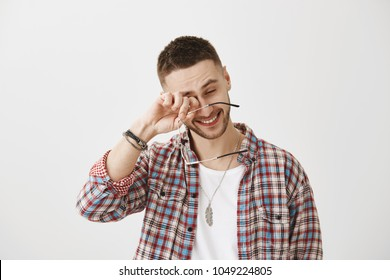 You made me laugh to tears. Happy good-looking unshaved male holding glasses while rubbing eyes, smiling while talking with colleague over gray background. Guy sits all day in front of laptop