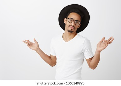 You may dismiss. Portrait of attractive young dark-skinned male snob, feeling self-assured and arrogant, bragging about success and fashion, spreading hands, standing in glasses and black hat