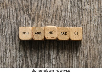 """""""YOU AND ME ARE US"""" printed on vintage wooden dice flat lay over head view with rustic wood background"""