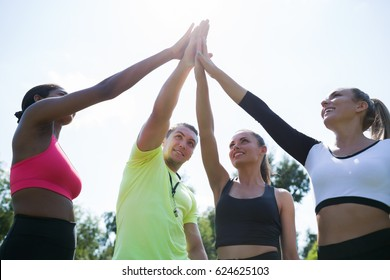 You are my champions. Group circle of  happy athletic young women in sportswear holding hands together with coach in green summer park  outdoors