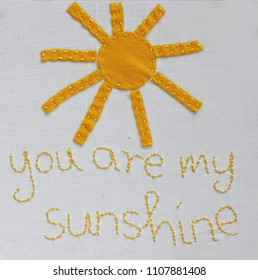 """You are my sunshine"" embroidered on linen fabric and sun crafted of felt"