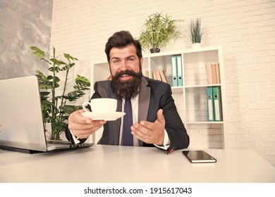 You need some caffeine. Happy hipster serve coffee in office. Director hold hot cup at desk. Caffeine energy. Caffeine addiction. Caffeine wakes you up. Morning drink. Breakfast tea. - Shutterstock ID 1915617043