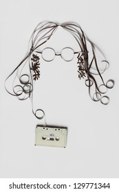 You need is tape. A beautiful image made of tape cassette with the tape forming a face of hair glasses on bright background.