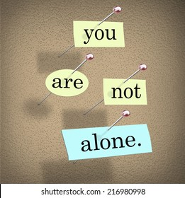 You Are Not Alone words on paper pinned to a bulletin board assuring you you're part of a community or team