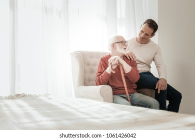 Are you OK. Interested caring handsome man sitting on the chair talking to his father and spending time together.