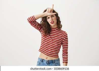 You are outsider. Studio shot of annoyed good-looking woman, feeling cool and confident while tilting head and showing loser-sign over forehead, standing with disrespectful expression over gray wall