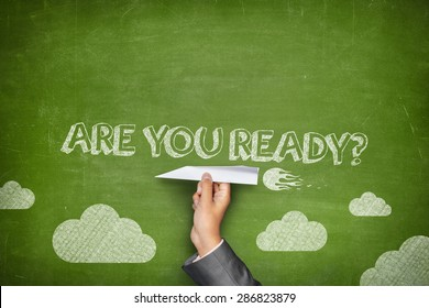 Are you ready concept on green blackboard with businessman hand holding paper plane