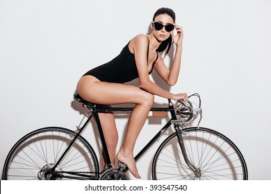 Are you ready to go? Side view of beautiful young woman in black swimsuit adjusting her sunglasses while sitting on the bicycle against white background