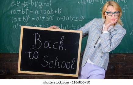 Are you ready to study. Beginning of new school season. Woman teacher holds blackboard inscription back to school. Lady educator in classroom wonders you ready to study. Teacher welcomes school year.